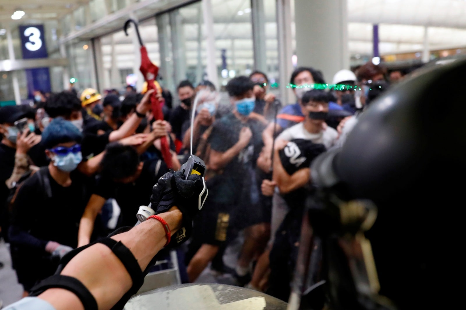 Riot police use pepper spray to disperse anti-extradition bill protesters during a mass demonstration after a woman was shot in the eye, at the Hong Kong international airport, in Hong Kong, China, August 13, 2019. REUTERS/Tyrone Siu