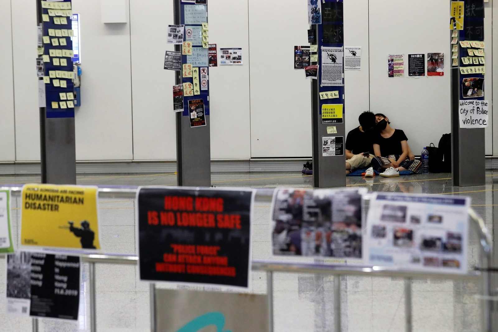 Anti-Extradition bill protesters couple sleep at arrival hall during a mass demonstration at the Hong Kong international airport, in Hong Kong, China, August 14, 2019. REUTERS/Tyrone Siu