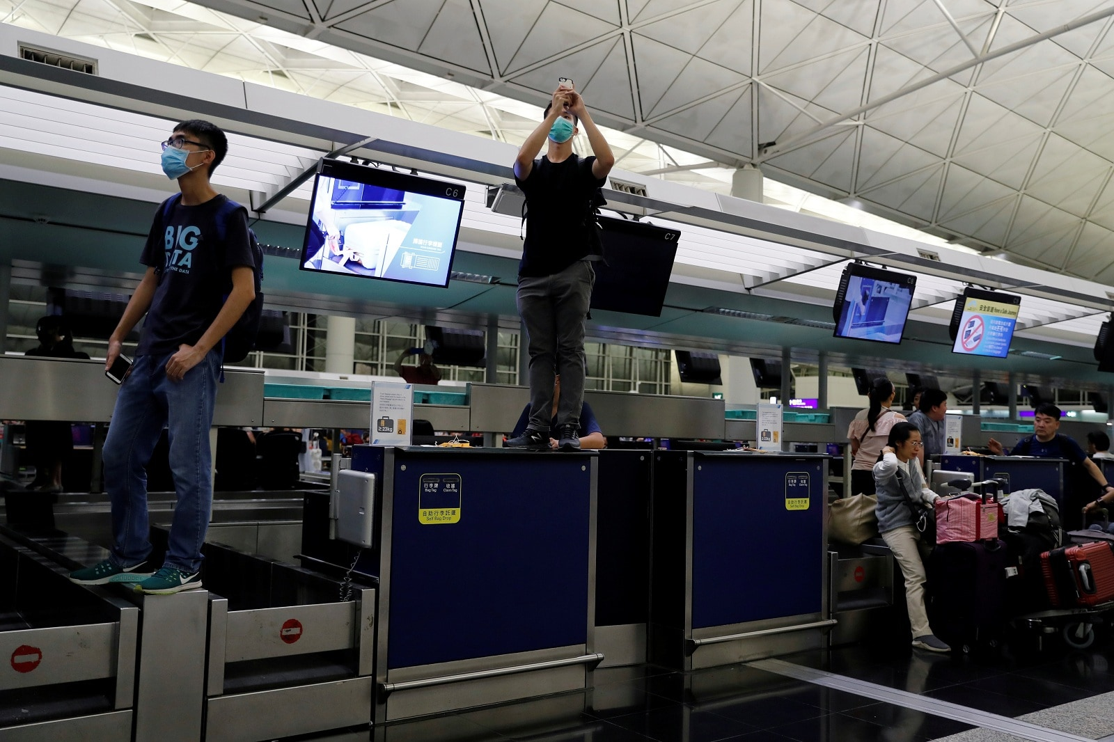 Anti-Extradition bill protesters are seen on the check-in counter during a mass demonstration at the Hong Kong international airport, in Hong Kong, China, August 13, 2019. REUTERS/Tyrone Siu