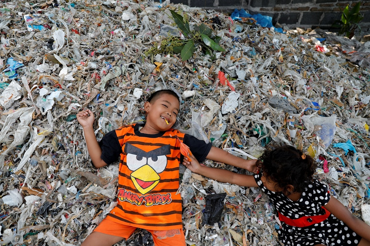 Children lay down as they play on a pile of rubbish at Bangun village in Mojokerto. REUTERS/Willy Kurniawan