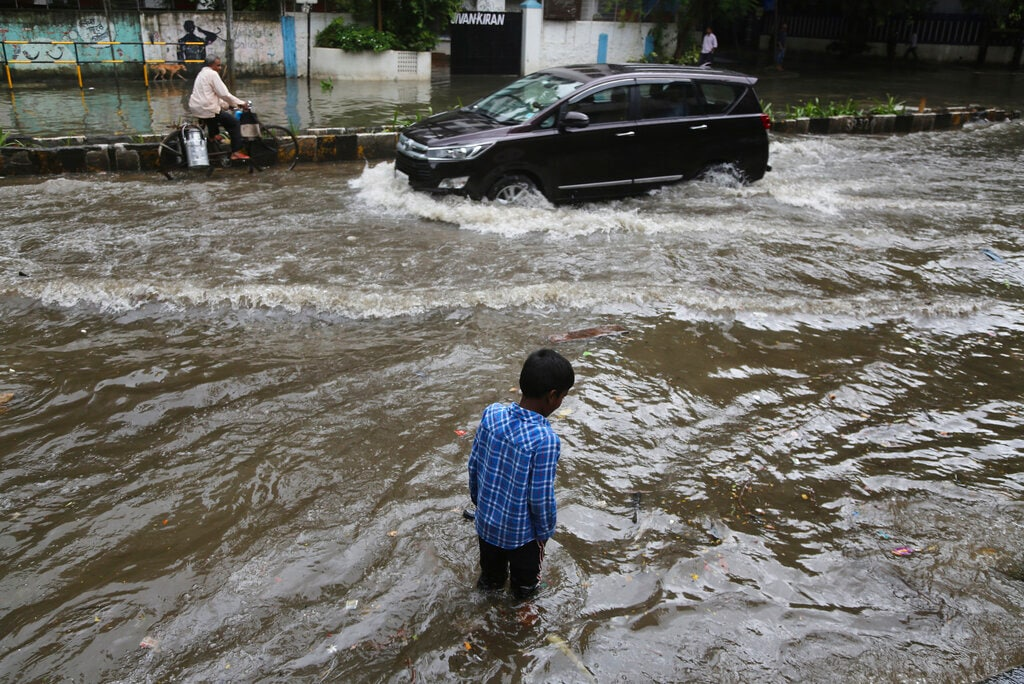 A boy wades through a waterlogged street after rainfall in Mumbai, India, Wednesday, July 24, 2019. India's monsoon season runs from June to September. (AP Photo/Rafiq Maqbool)