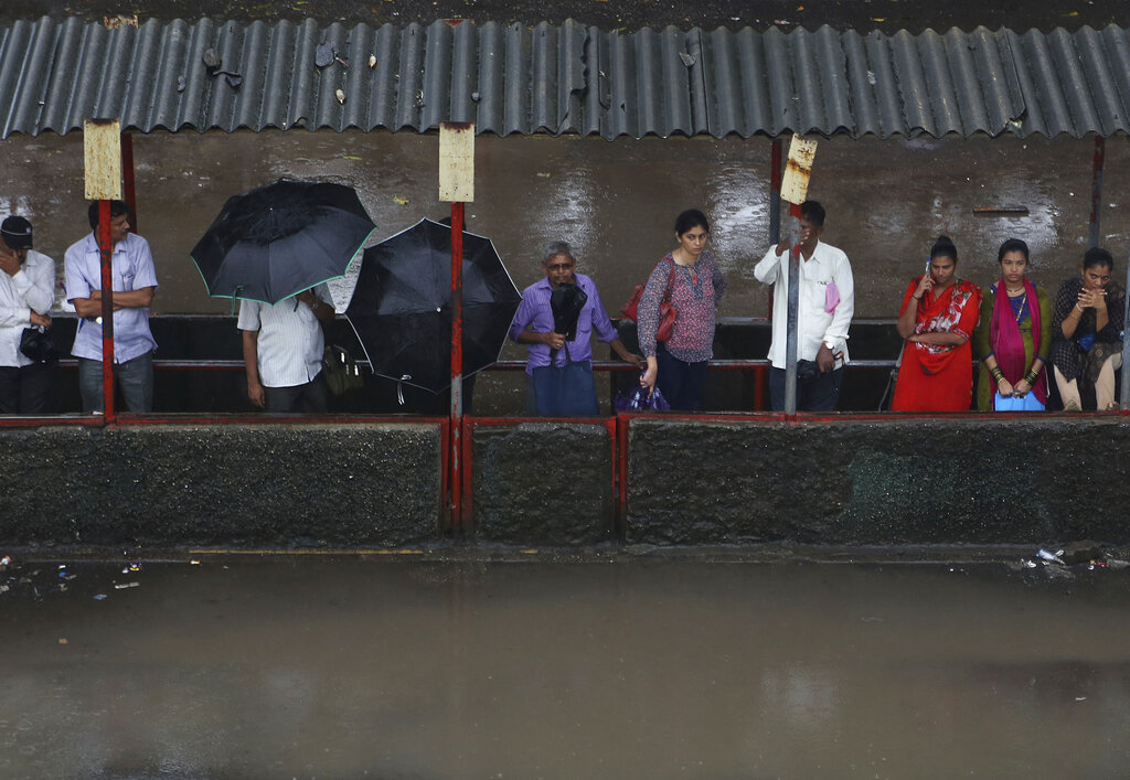 People wait for a bus at a waterlogged bus stop in Mumbai, India, Wednesday, July 24, 2019. India's monsoon season runs from June to September. (AP Photo/Rafiq Maqbool)