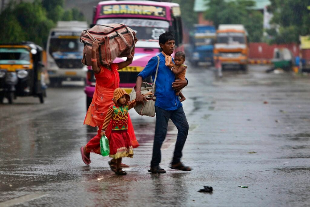 An Indian family crosses a street during rains in Jammu, India, Thursday, July 25, 2019. The annual monsoon rains are crucial for the rain-fed crops planted during the season. (AP Photo/Channi Anand)
