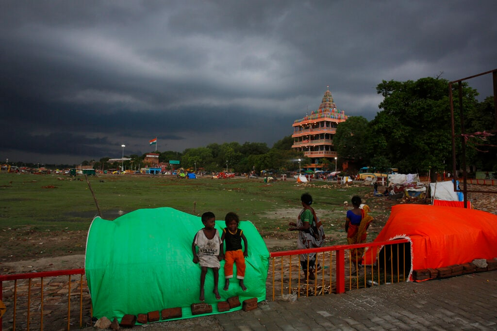 Children play by the banks of the River Ganges with monsoon clouds hovering over the region in Prayagraj, India, Thursday, July 25, 2019. India's monsoon rains last from June to September. (AP Photo/Rajesh Kumar Singh)