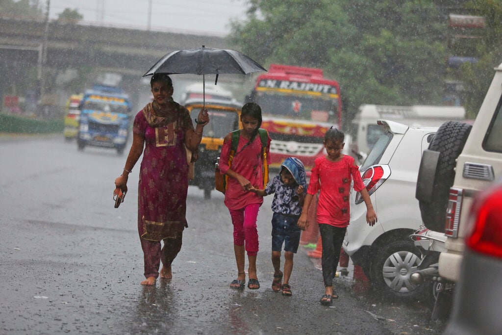 Pedestrians walk in the rain in Jammu, India, Saturday, July 27, 2019. The monsoon season in India lasts from June to September. (AP Photo/Channi Anand)