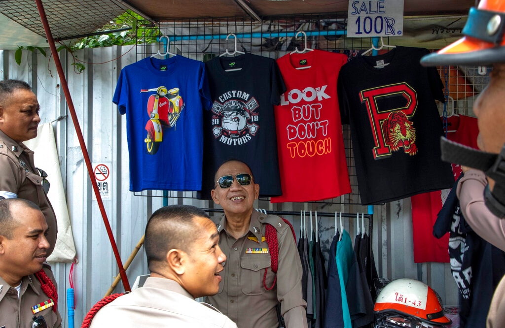 Police officers assigned to control traffic take a break at a street-shop outside the venue scheduled to hold of Association of Southeast Asian Nations, (ASEAN) annual leaders' summit in Bangkok, Thailand, Tuesday, July 30, 2019. (AP Photo/Gemunu Amarasinghe)