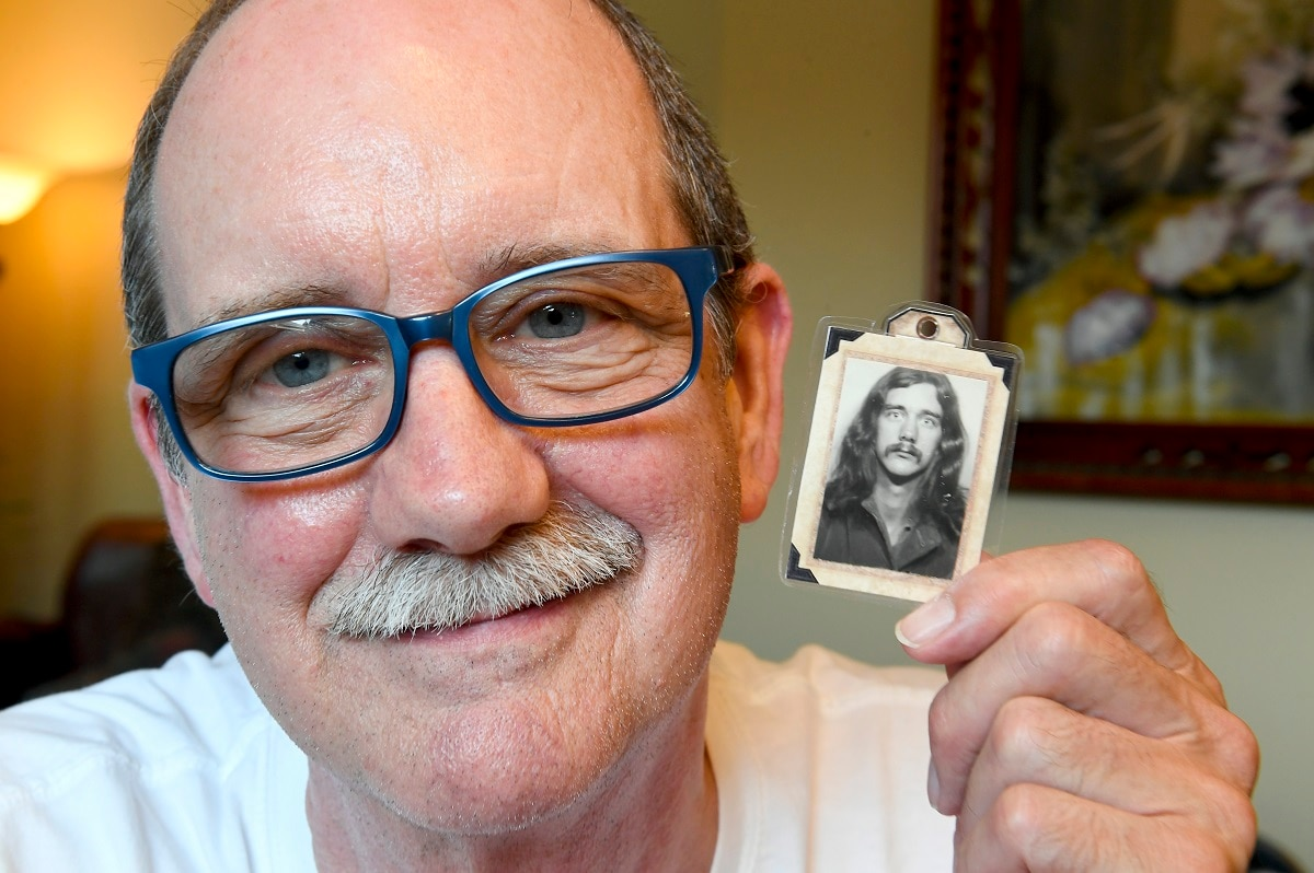 Kevin Rheden poses for a photograph with a photo of himself taken while in high school as he talks about his memories of the original Woodstock music festival. (AP Photo/Hans Pennink)