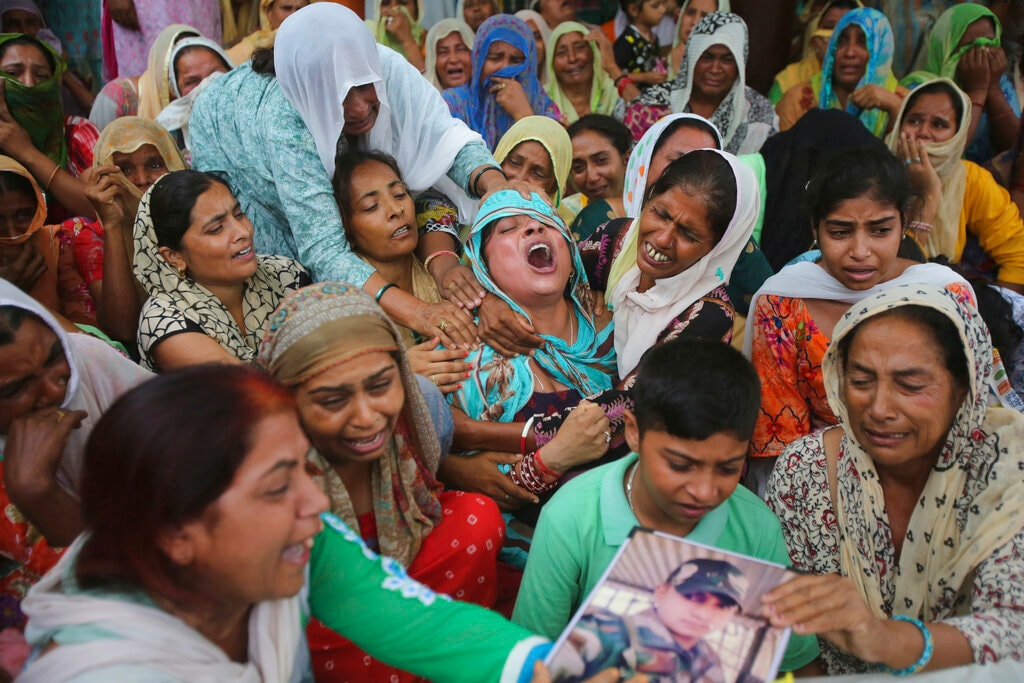 In this Wednesday, July 31, 2019, file photo, a woman, center, wails by the body of her husband, an Indian army soldier Krishan Lal who was killed in firing from the Pakistan side of the border, at Ghagriyal village, in Akhnoor, about 62 kilometers (51 miles) from Jammu, India. Indian and Pakistani soldiers on Tuesday traded heavy gunfire across a cease-fire line dividing Kashmir between the hostile neighbours, leaving one Indian soldier and one Pakistani civilian dead and several others wounded, officials said. (AP Photo/Channi Anand, File)