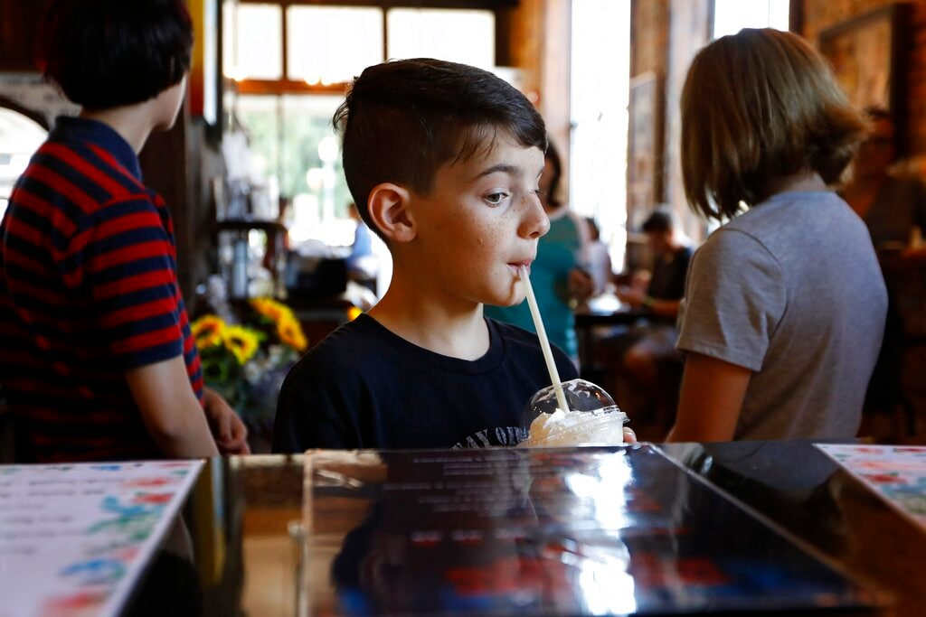 In this Friday, July 26, 2019 photo, Ethan Curtis, a 10-year-old Stranger Things fan from San Antonio, eyes the Stranger Drinks menu while sipping on a Sheriff Hopper specialty drink at Lucy Lu's Coffee Cafe in Jackson, Ga. Behind him, family members Emilynn Guthrie, 9, and Layla Curtis, 13, are dressed like characters Mike and Eleven from Stranger Things. Lucy Lu's employees said the themed menu is popular among locals and fans who visit to see filming locations. (AP Photo/Andrea Smith)