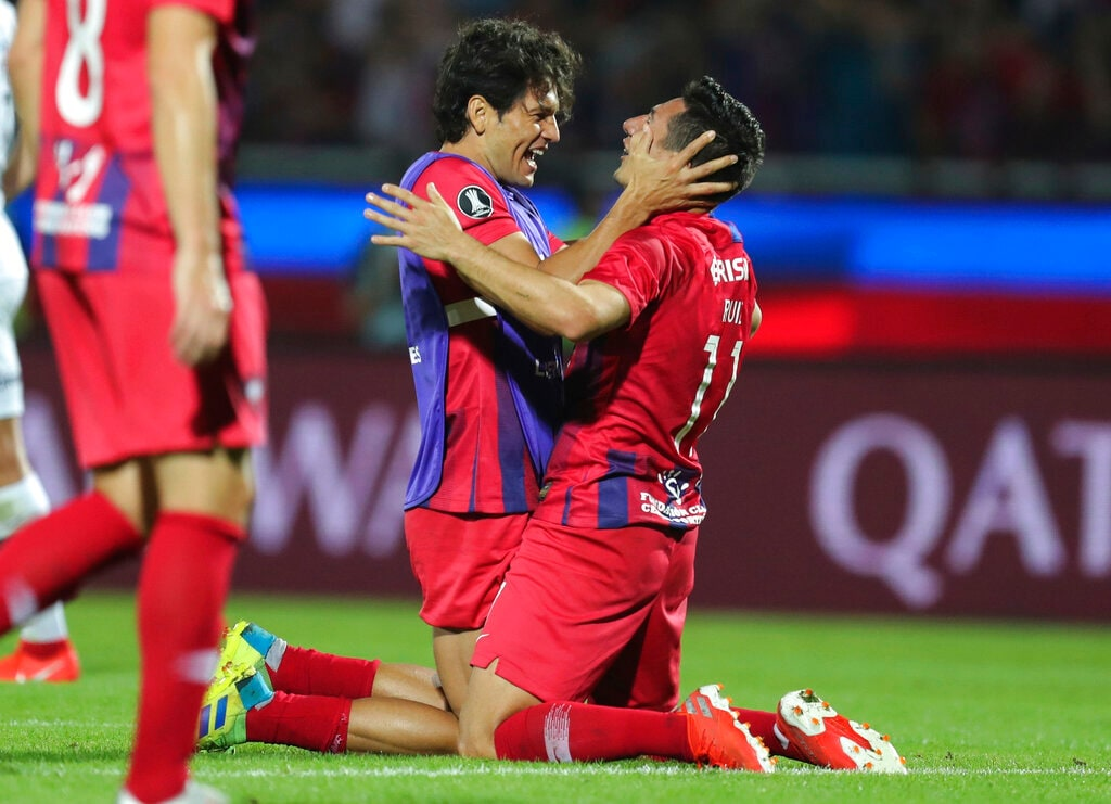 Nelson Haewdo, left, and Oscar Ruiz, of Paraguay's Cerro Porteno, celebrate their 2-1 victory over Argentina's San Lorenzo at the end of a Copa Libertadores soccer match in Asuncion, Paraguay, Wednesday, July 31, 2019. Cerro Porteno passes to the next round. (AP Photo/Jorge Saenz)