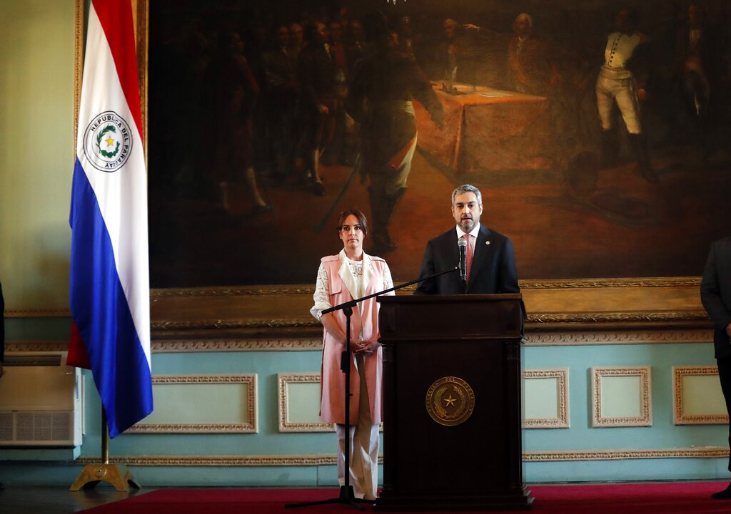 Paraguay's President Mario Abdo Benitez speaks to the nation, accompanied by his wife Silvana Lopez Moreira, from the Palacio de Lopez in Asuncion, Paraguay, Thursday, Aug. 1, 2019. Paraguay and Brazil have scrapped a widely criticized agreement on sharing power from a hydroelectric dam that led to the resignation of Paraguay's foreign minister and called for the impeachment of Abdo Benitez. (AP Photo/Jorge Saenz)