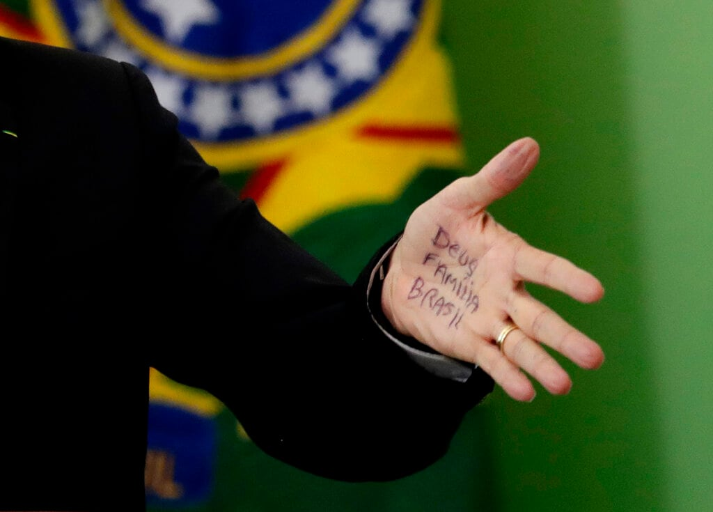 The hand of Brazilian President Jair Bolsonaro shows keywords that read in Portuguese: