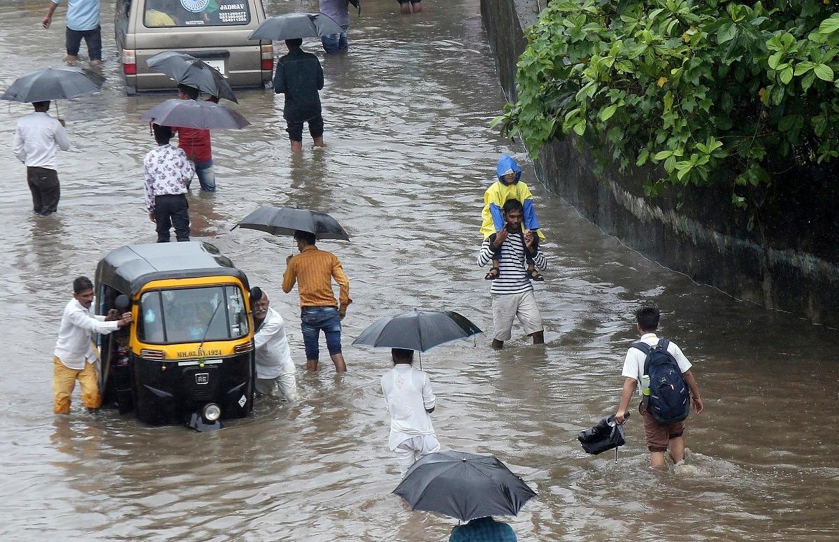 Commuters navigate their way through a flooded street in Mumbai. (AP Photo/Rajanish Kakade)