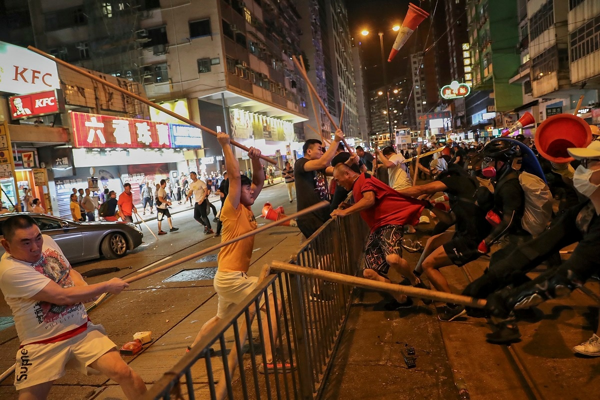Protesters wearing black shirt, right, fight with a group of men wielding wooden poles on a street during the anti-extradition bill protest at a neighbourhood in Hong Kong. China warned that it will be
