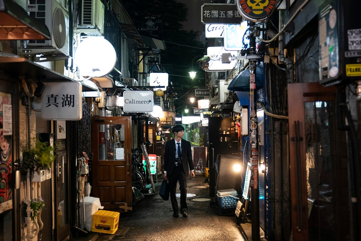 A man strolls through a narrow alleyway clustered with tiny bars and restaurants at the Golden Gai. (AP Photo/Jae C. Hong)