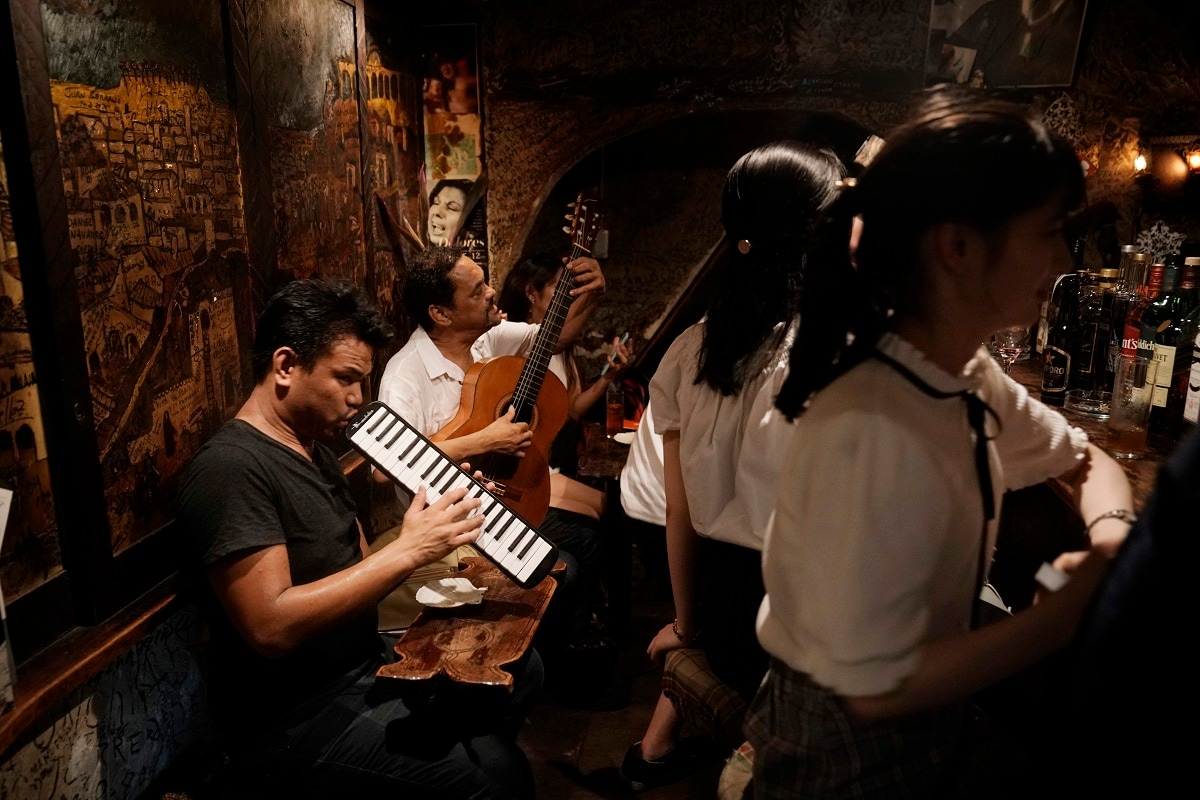 Two musicians entertain patrons in a tiny bar at the Golden Gai in the Shinjuku district of Tokyo. (AP Photo/Jae C. Hong)