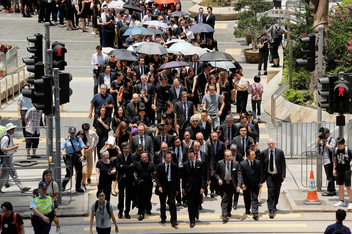 Lawyers cross a street during a protest march in Hong Kong. The head of Beijing's Cabinet office responsible for Hong Kong says the territory is facing its