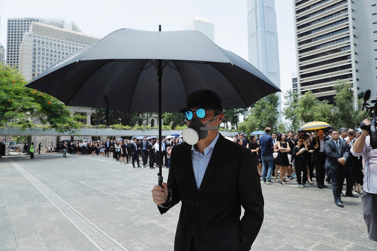 A man carries an umbrella and wears a face mask as lawyers gather for a protest march in Hong Kong. Zhang Xiaoming, head of Beijing's Cabinet office responsible for the territory, said the protests are getting increasingly violent and having
