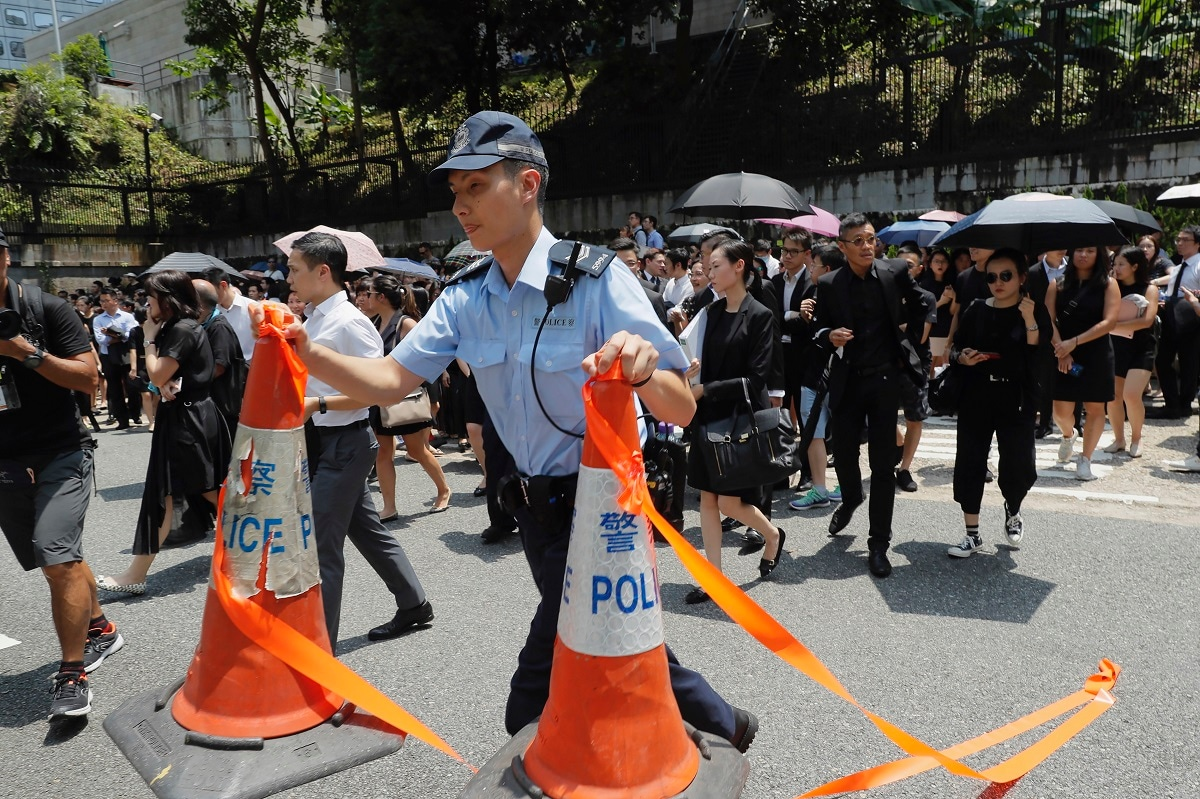 A policeman moves traffic cones as lawyers walk during a protest march in Hong Kong. Hong Kong was returned to China under the framework of