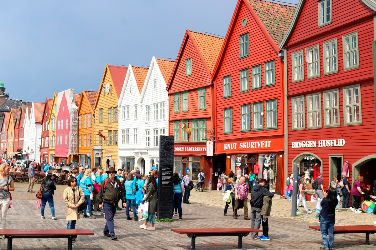 The image shows people walking by the historic buildings of Bryggen, the old wharf area of Bergen, Norway. A trip on a cruise ship in spring and summer provides a close view of the high cliffs that tower over the narrow inlets. Unlike cruises that spend long periods at sea between ports, a trip through Norway's fjords provides ever-changing scenery, with no need for a strenuous hike. (AP Photo/Brian Witte)