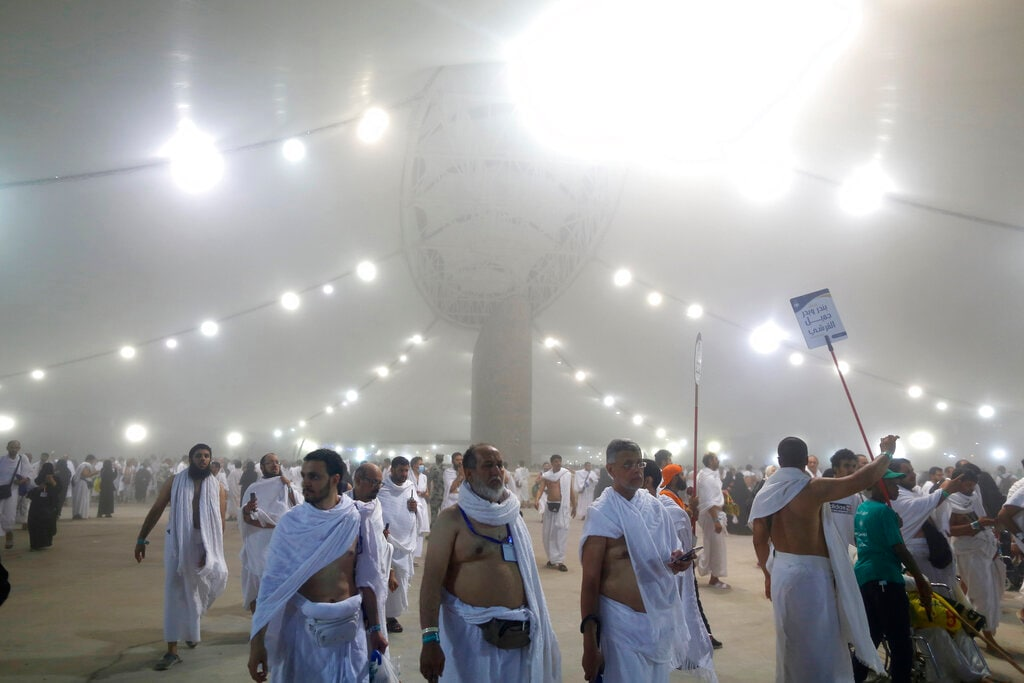 Muslim pilgrim walk after they cast stones at a pillar symbolizing the stoning of Satan, in a ritual called