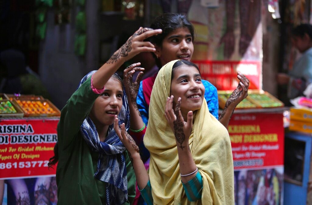 Girls gesture after getting henna decorations on their hands on the eve of Eid al Adha, in Jammu, India, Sunday, Aug.11, 2019. (AP Photo/Channi Anand)