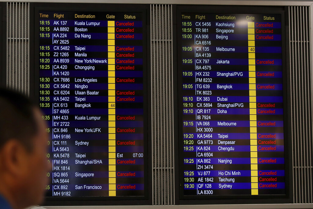 A man looks at the flight information board shows outbound flights was cancel at the Hong Kong International airport, Monday, Aug. 12, 2019. One of the world's busiest airports cancelled all remaining flights for the day after thousands of pro-democracy protesters crowded into the main terminal. (AP Photo/Vincent Thian)