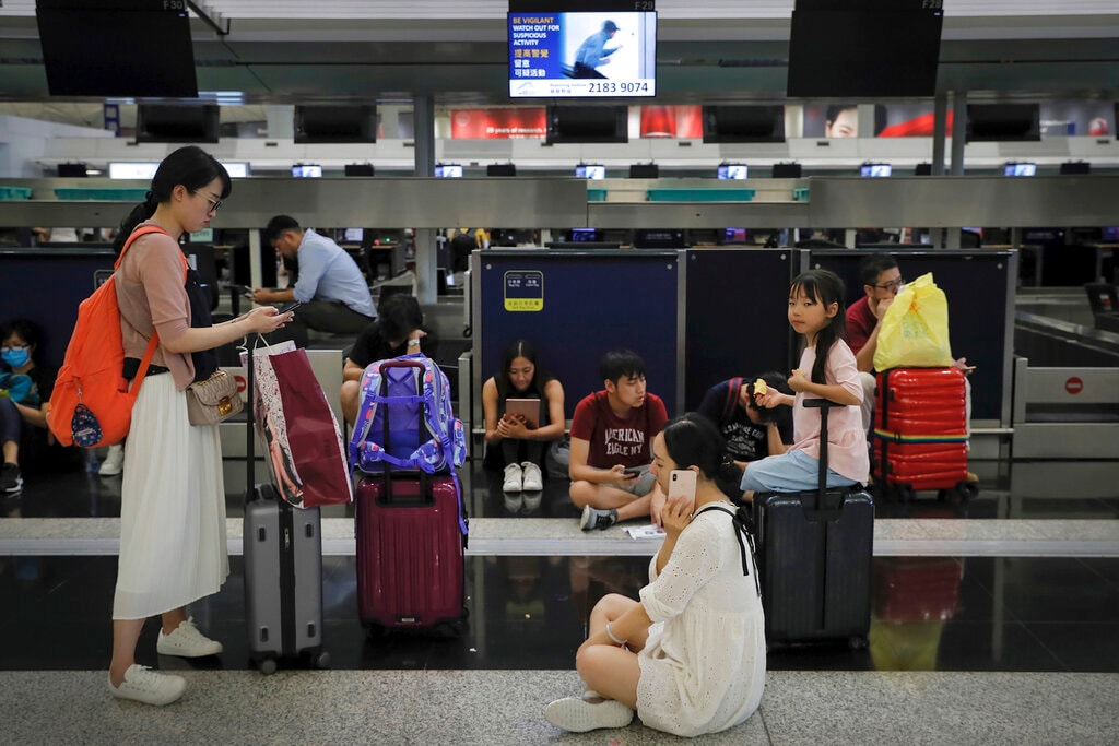 Travelers gather at the closed check-in counters as protesters stage a protest at the Hong Kong International Airport, Monday, Aug. 12, 2019. (AP Photo/Kin Cheung)