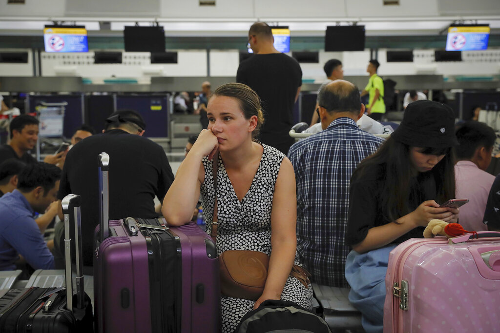 Australian Penny Tilley, center, reacts next to stranded travelers at the closed check-in counters at the Hong Kong International Airport, Monday, Aug. 12, 2019. (AP Photo/Kin Cheung)