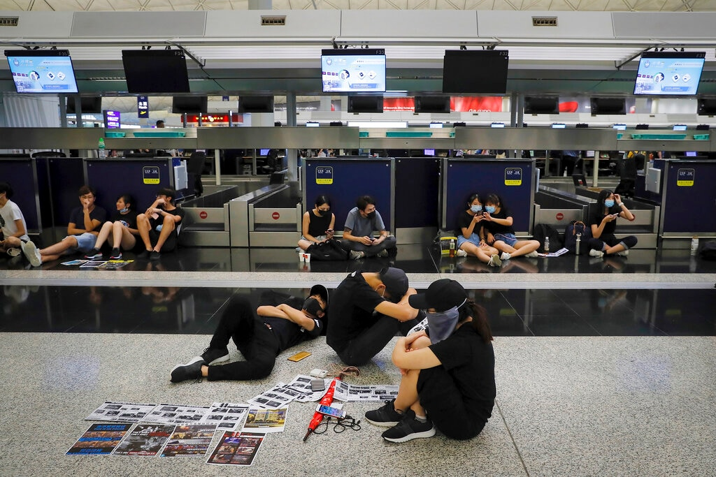 Protesters gather at the closed check-in counters at the Hong Kong International Airport, Monday, Aug. 12, 2019. (AP Photo/Kin Cheung)