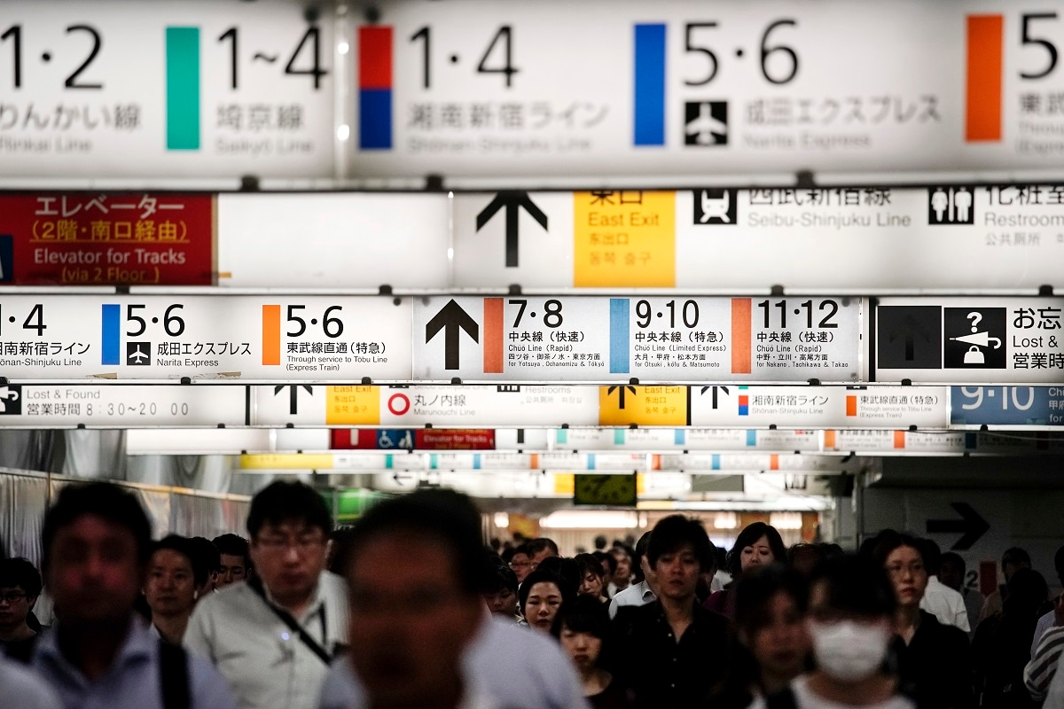 Commuters make their way through a tunnel underneath the clusters of platform signs at Shinjuku Station during morning rush hours in Tokyo. Tokyo has one of the most advanced public transport systems in the world, but with less than one year to go before the city hosts the 2020 Olympic Games, local governments, companies and commuters are bracing for unprecedented strain the events could put on rail transit and highways. (AP Photo/Jae C. Hong)
