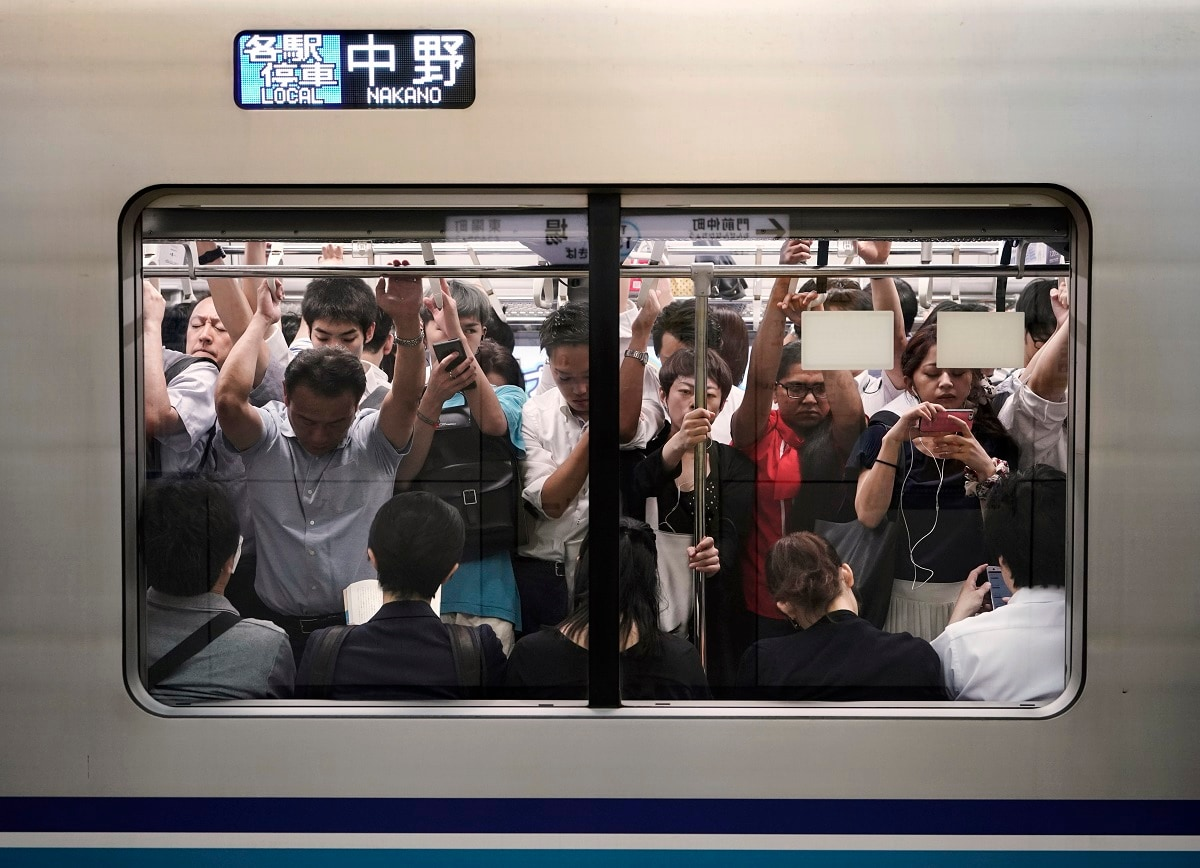 Commuters are seen through the window of an overcrowded train during morning rush hours at Kiba Station in Tokyo. (AP Photo/Jae C. Hong)