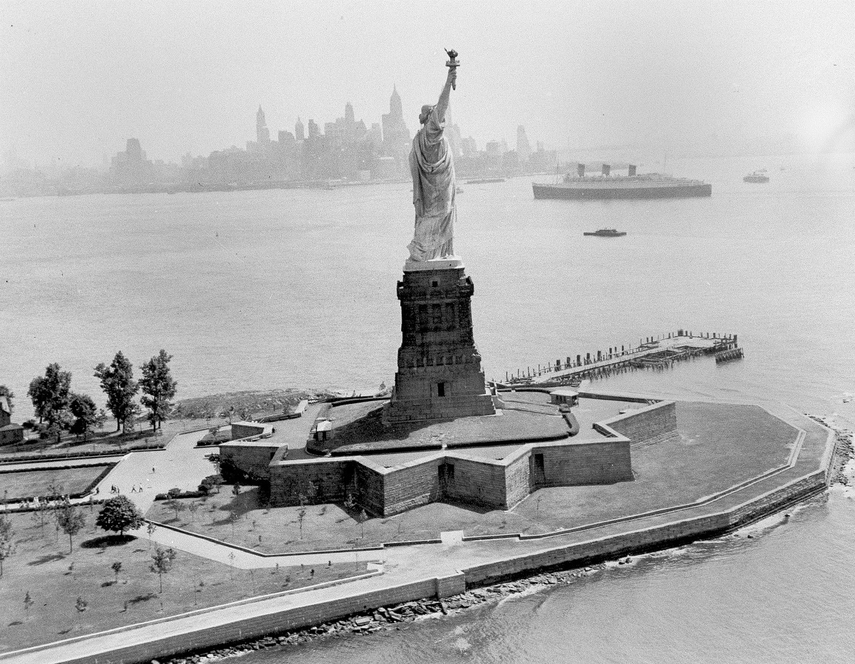 The Statue of Liberty stands in New York Harbor as the ocean liner Queen Mary goes past as seen from a US Coast Guard helicopter. (AP Photo/File)