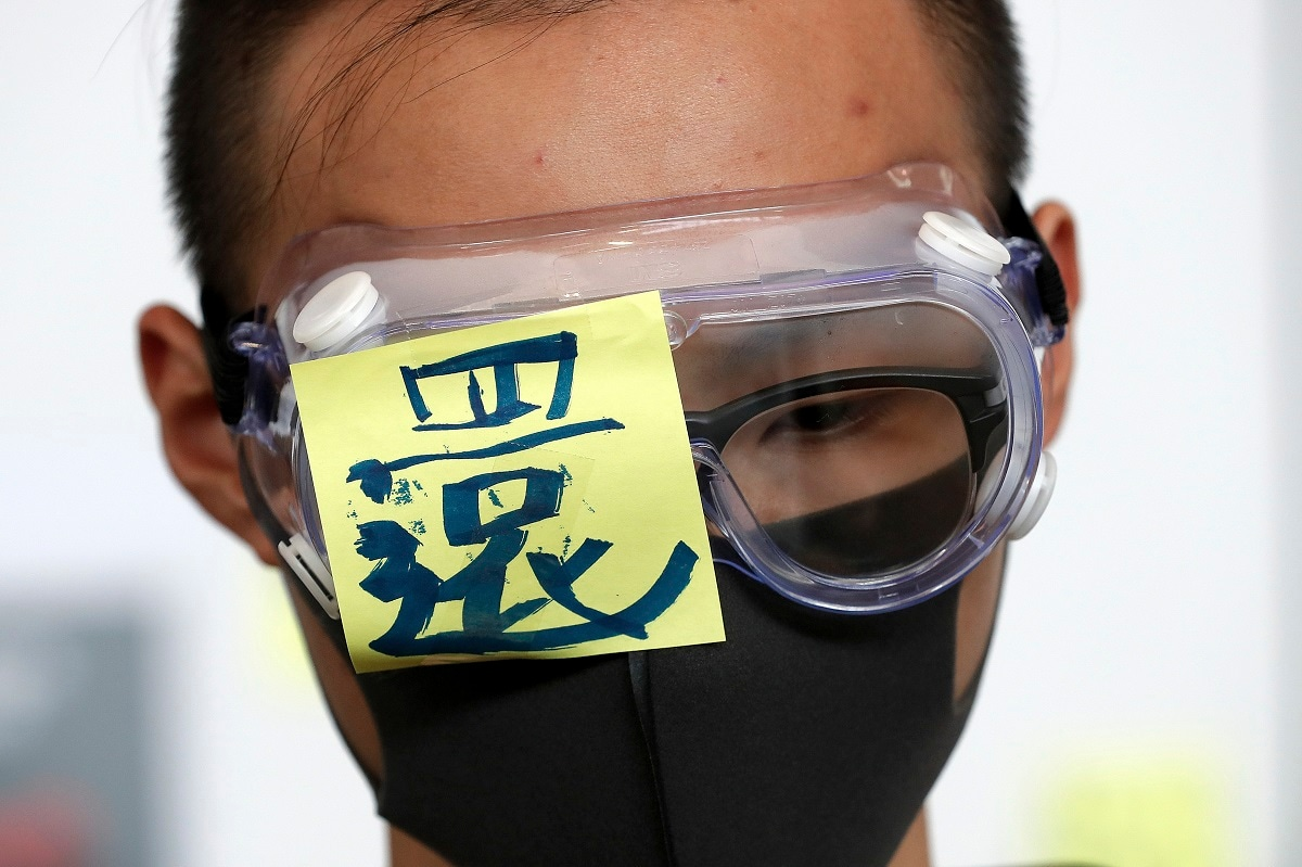 A protester wears a goggle with the word