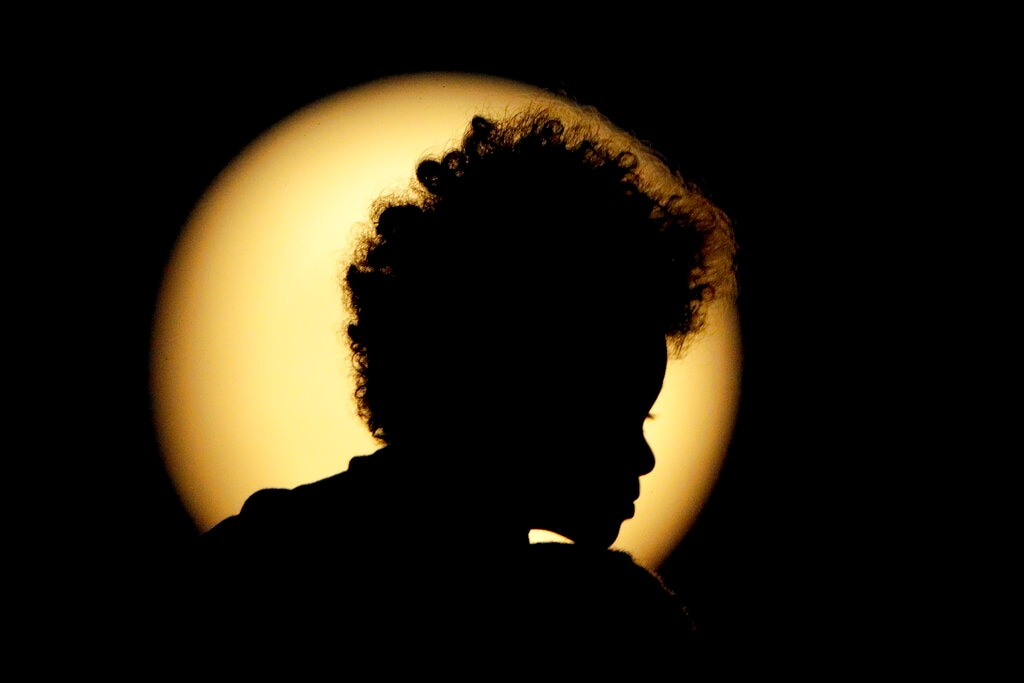 A boy is silhouetted against the full moon as it rises beyond downtown Kansas City, Mo. Wednesday, Aug. 14, 2019. (AP Photo/Charlie Riedel)