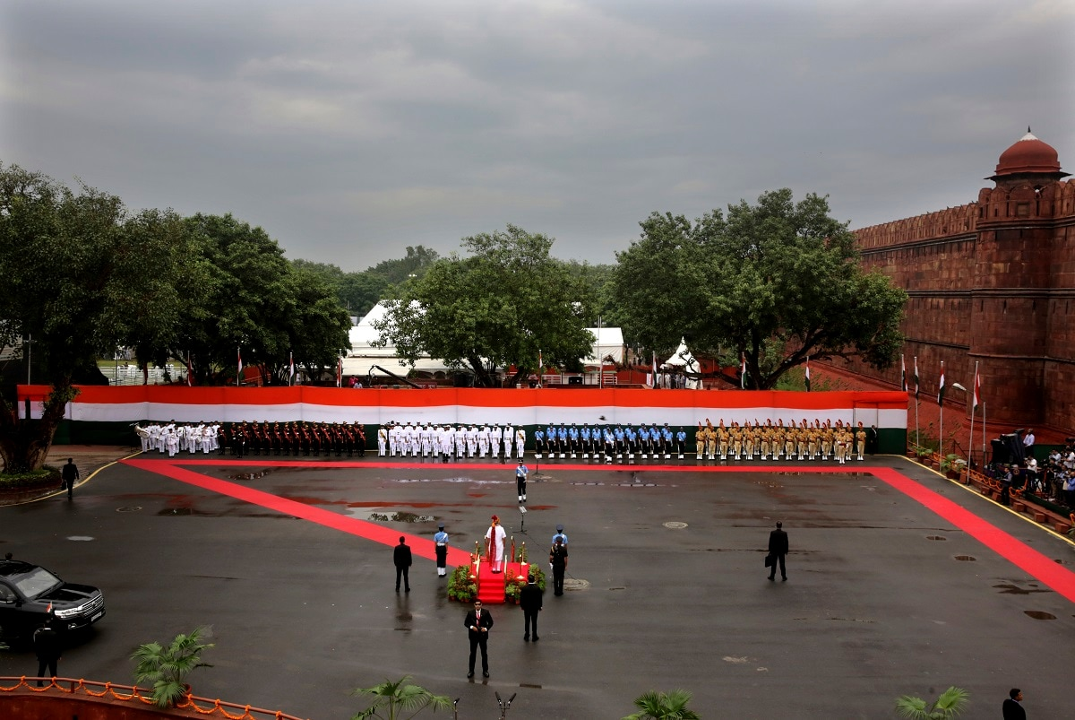 Indian Prime Minister Narendra Modi, centre in white, takes a joint military guard of honour before addressing the nation on the country's Independence Day from the ramparts of the Mughal-era Red Fort, in New Delhi. (AP Photo/Manish Swarup)
