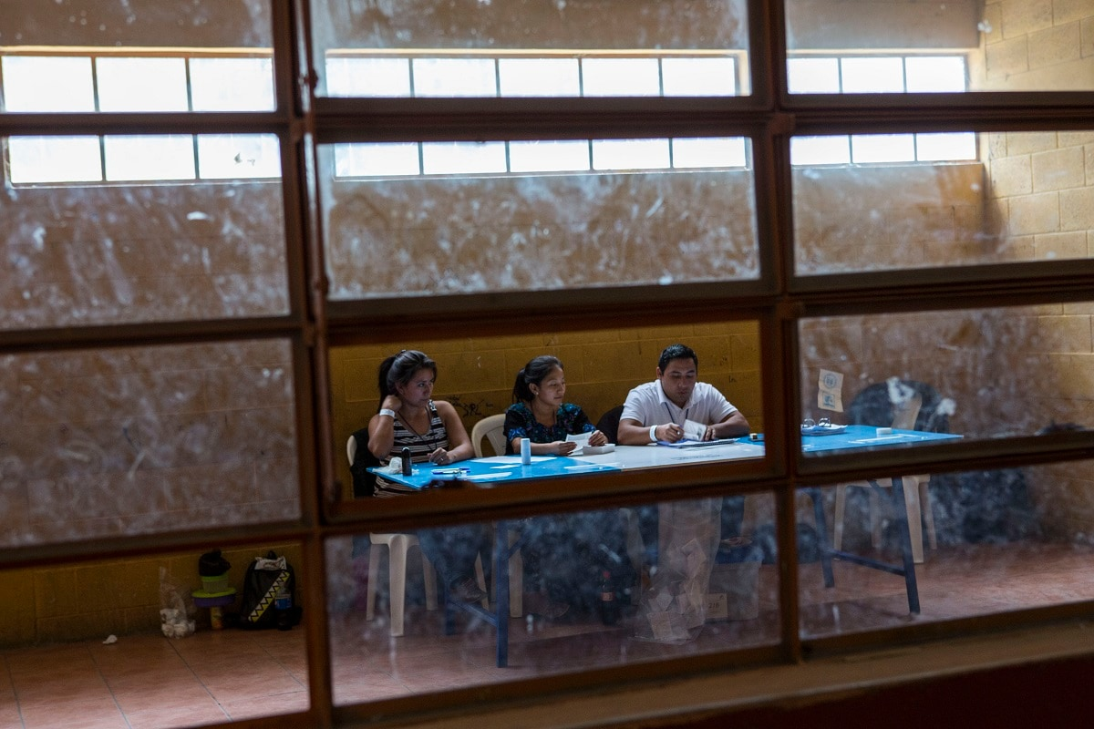 Electoral workers wait for people to cast their votes in Chinautla, on the outskirts of Guatemala City. Guatemalans go the polls Sunday in the second-round presidential runoff, pitting ex-first lady Sandra Torres against conservative Alejandro Giammattei in a nation beset by poverty, unemployment and emigration. (AP Photo/Oliver de Ros)