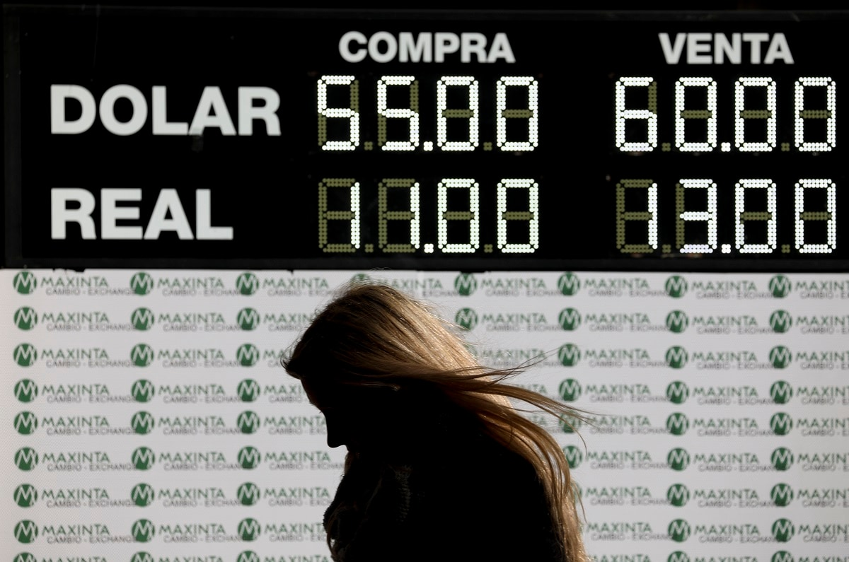 A woman walks past a currency exchange board in Buenos Aires, Argentina. The peso devalued sharply on Monday in Argentina after a striking victory by the opposition in Sunday's presidential primaries ahead of October's presidential elections. (AP Photo/Natacha Pisarenko)