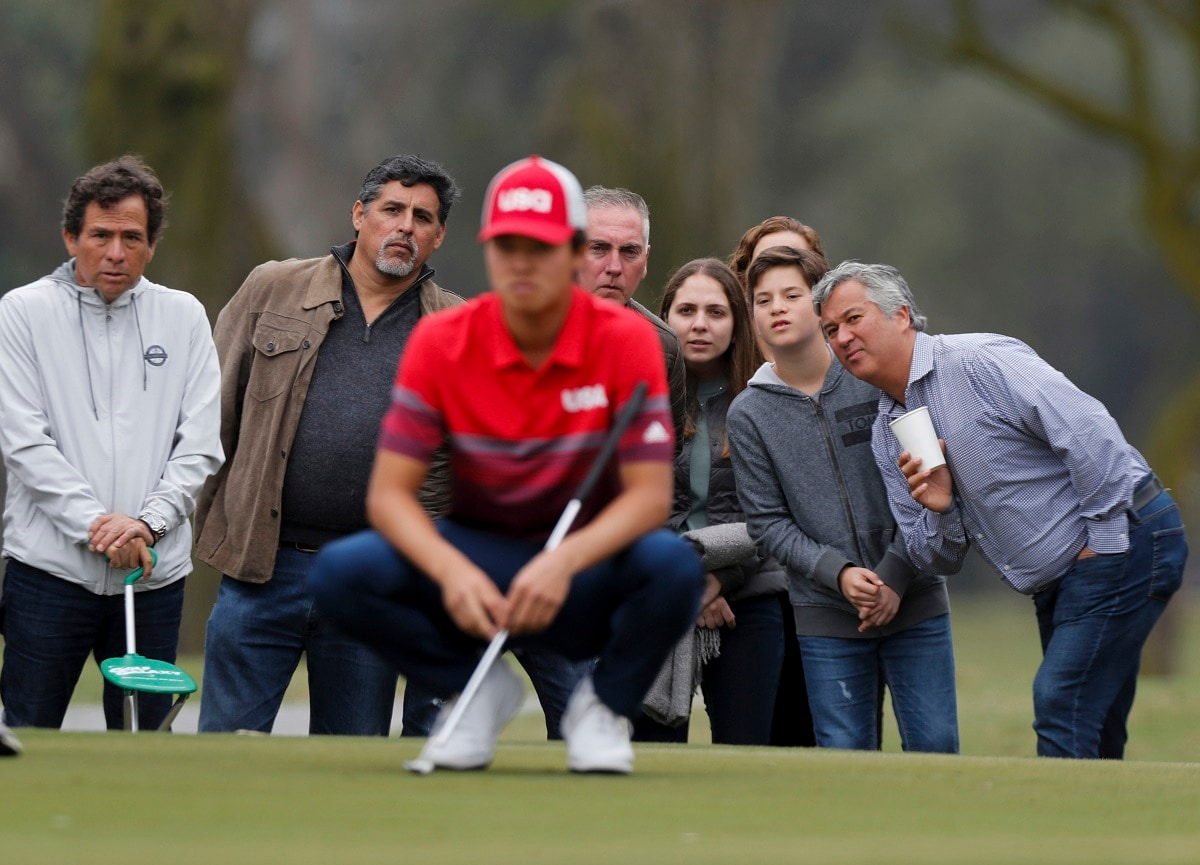 Spectators look as Brandon Wu of the United States, front, studies his putt at the second hole green during the men's golf final round at the Pan American Games in Lima, Peru. (AP Photo/Fernando Llano)