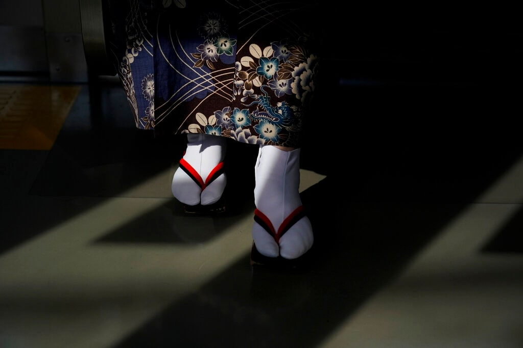 In this Friday, Aug. 16, 2019, file photo, a woman wearing kimono and traditional Japanese sandals called