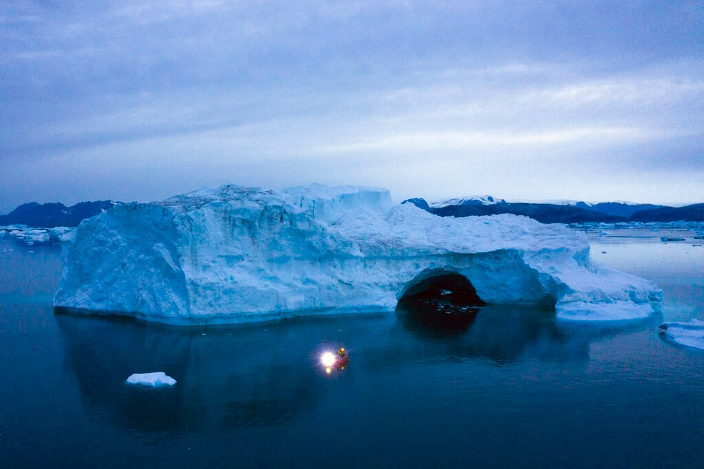 A boat navigates at night next to a large iceberg in eastern Greenland, late Friday, Aug. 15, 2019. Greenland has been melting faster in the last decade and this summer, it has seen two of the biggest melts on record since 2012. (AP Photo/Felipe Dana)