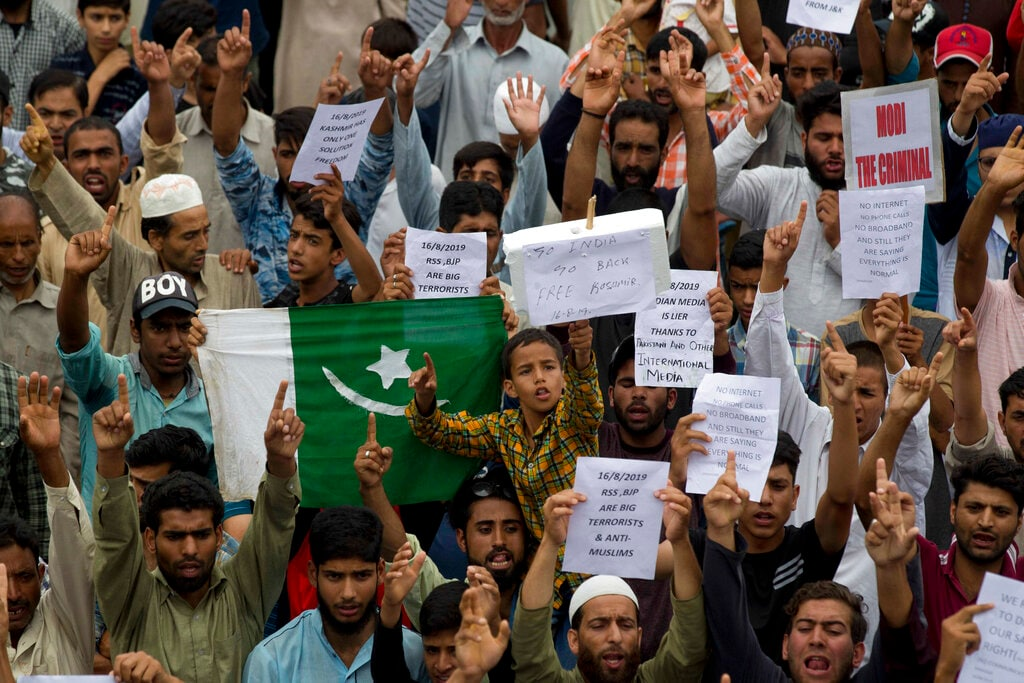 Kashmiri hold placards and shout pro-freedom slogans during a demonstration after Friday prayers amid curfew like restrictions in Srinagar, on August 16. (AP Photo/Dar Yasin)