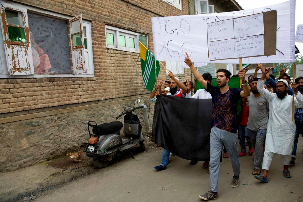 A Kashmiri Muslim woman, left, watches from her house as men hold placards and shout pro-freedom slogans during a demonstration after on August 16. (AP Photo/Dar Yasin)