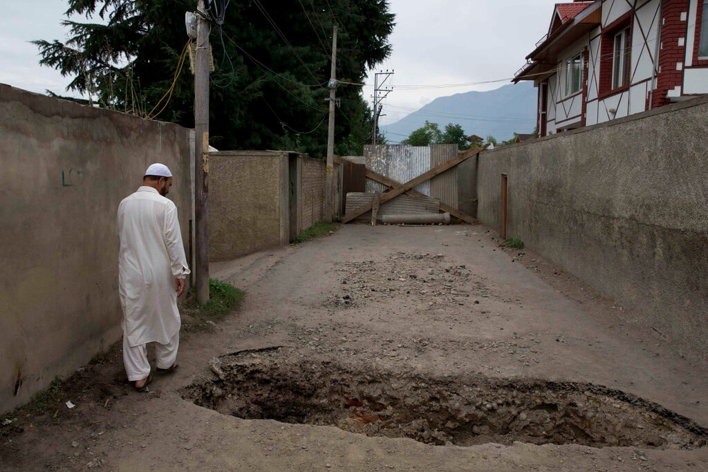 A Kashmiri man walks past a crater dug up by locals to prevent police vehicles enter the area, on August 16. (AP Photo/Dar Yasin)