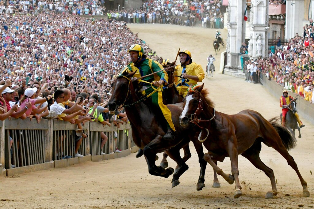 Remorex, without its jockey, right, on its way to win the horse race Palio di Siena, in Siena, Italy, Friday, Aug. 16, 2019. (Claudio Giovannini/ANSA Via AP)