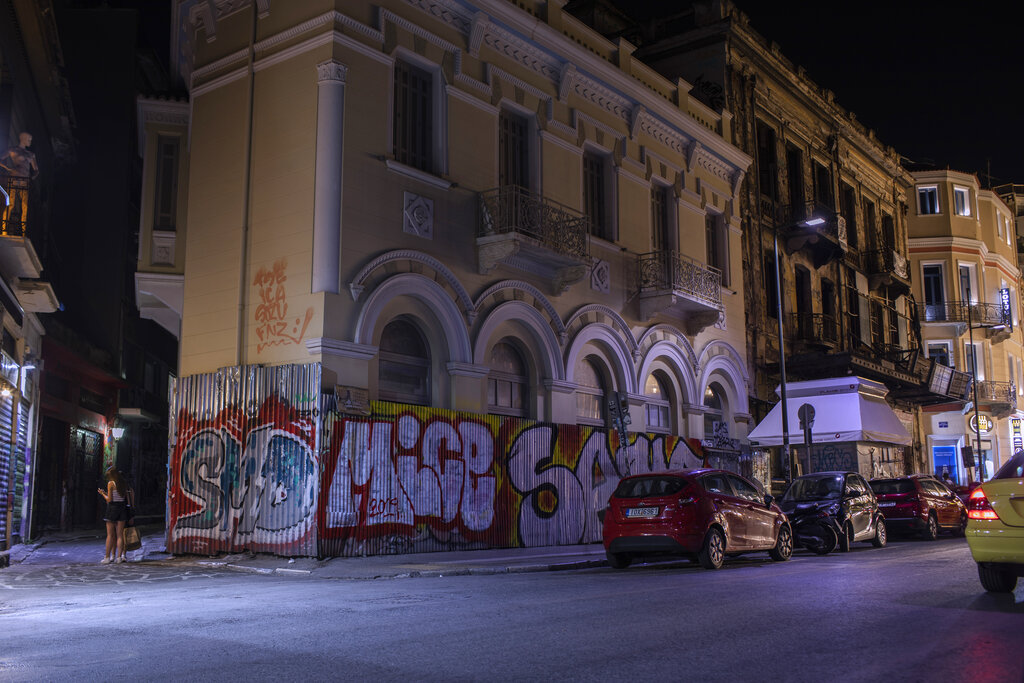 In this Sunday, July 7, 2019 photo, the fence of a renovated building and part of the wall are defaced with graffiti in Monastiraki district, central Athens. (AP Photo/Petros Giannakouris)