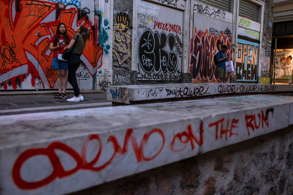 In this Friday, July. 26, 2019 photo, a marble-topped wall round the 11th Century AD Panagia Kapnikarea church and a shop that has been closed for months are covered with graffiti in Athens' Ermou main shopping street. While Athens has acquired many striking murals by artists commissioned by public bodies or private property owners, most of the new graffiti is unsolicited, devoid of visible meaning and cacophonous - a jostling mass of individual