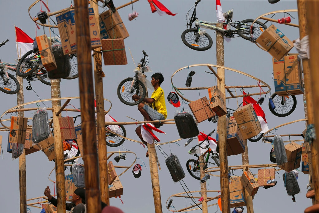 An Indonesian man retrieves his prize after climbing up a greased pole during a greased-pole climbing competition held as part of Independence Day celebrations at Ancol Beach in Jakarta, Indonesia. Saturday, Aug. 17, 2019. Indonesia is celebrating its 74th anniversary of independence from the Dutch colonial rule. (AP Photo/Tatan Syuflana)