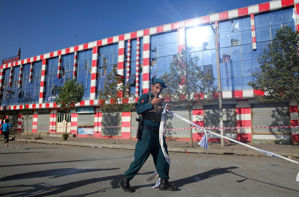 An Afghan policeman stands guard outside a damaged Dubai City wedding hall after an explosion in Kabul, Afghanistan, Sunday, Aug. 18, 2019. (AP Photo/Rafiq Maqbool)