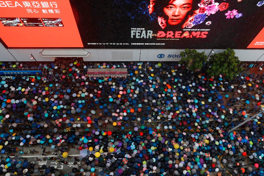 In this Sunday, Aug. 18, 2019, file photo, demonstrators carry umbrellas as they march along a street in Hong Kong. Heavy rain fell on tens of thousands of umbrella-ready protesters as they started marching from a packed park in central Hong Kong, where mass pro-democracy demonstrations have become a regular weekend activity. (AP Photo/Vincent Yu, File)